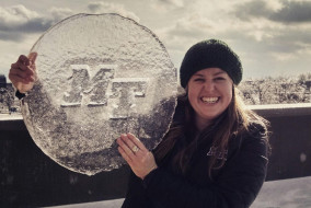 Senior Tressa Spingler posed with a frozen MT logo on the roof of the Champion Way Garage on Feb. 17. This was during the second of three consecutive school closings at MTSU due to winter weather. (Rhiannon Gilbert/MTSU Sidelines)