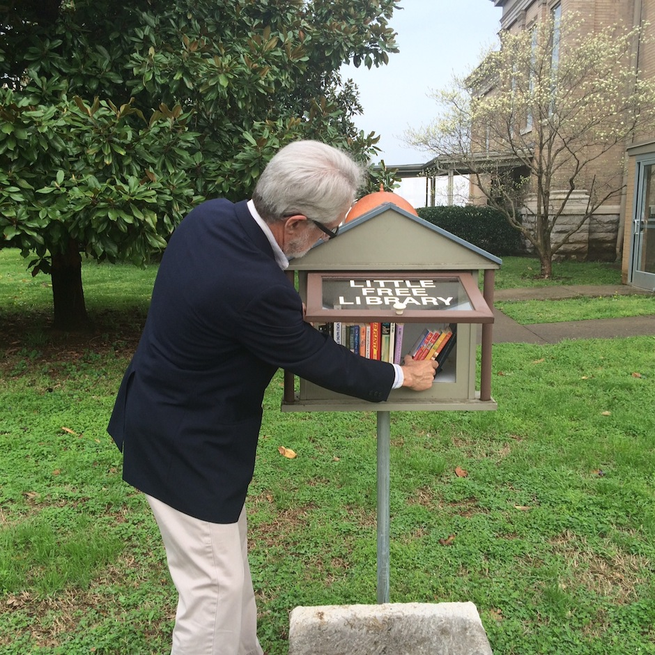 Pastor Steve Odom rearranges books in the Little Free Library beside Central Christian Church on April 7, 2015. (Rhiannon Gilbert/ MTSU Sidelines)