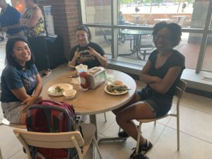 Three young women gather at a table in the Farmers Market to enjoy the fresh food.