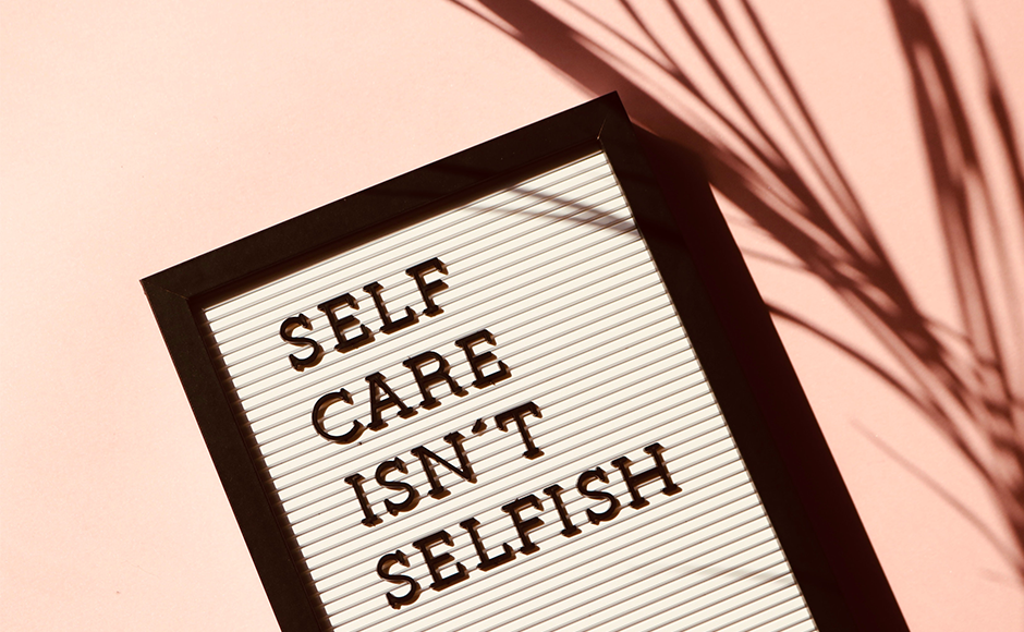 "A letterboard lays against a pink background: it says ""self-care isn't selfish"""