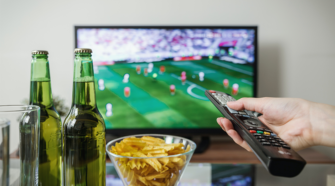 a hand holds a remote towards a TV, with American soccer on the screen. Snacks and drinks line the foreground of the photo.