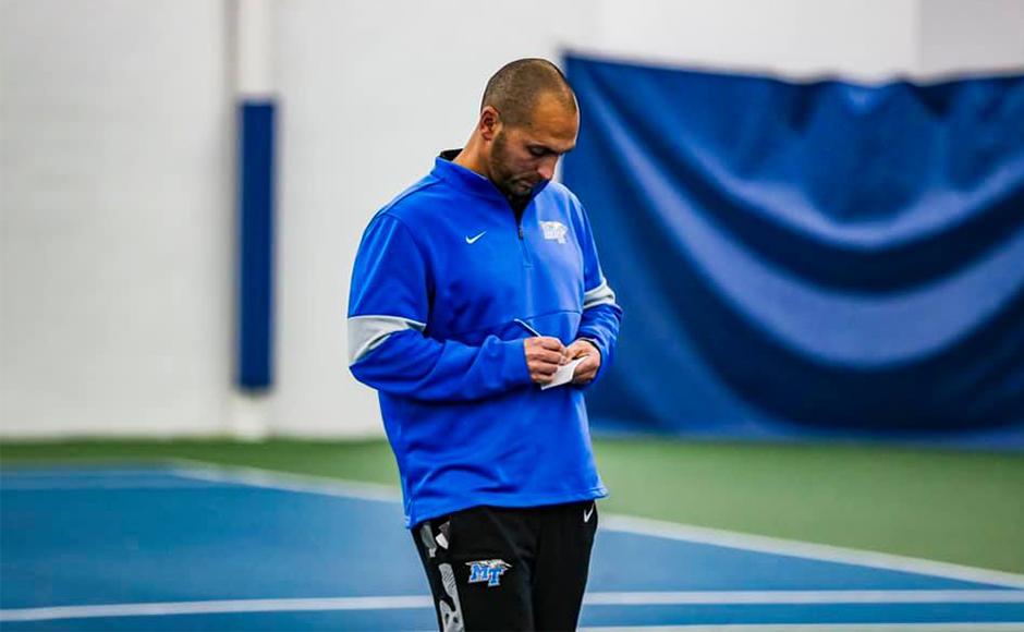 MTSU Men's Tennis coach Jim Boredame stands on a tennis court while writing a note.
