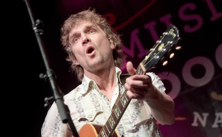 Brendan Benson plays the guitar on stage.